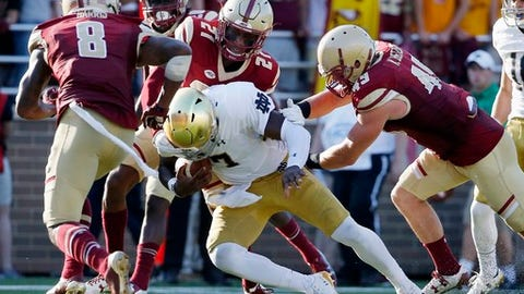 Boston College's Will Harris (8), Lukas Denis (21) and Kevin Bletzer (49) stop Notre Dame's Brandon Wimbush (7) on a carry during the first half of an NCAA college football game in Boston, Saturday, Sept. 16, 2017. (AP Photo/Michael Dwyer)