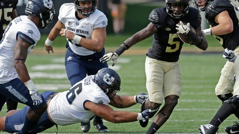 Wake Forest's Arkeem Byrd (5) runs past Utah State's Gasetoto Schuster (56) in the first half of an NCAA college football game in Winston-Salem, N.C., Saturday, Sept. 16, 2017. (AP Photo/Chuck Burton)