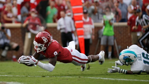 Oklahoma wide receiver CeeDee Lamb (9) dives into the end zone for a touchdown as Tulane's P.J. Hall during the first quarter of an NCAA college football game in Norman, Okla., Saturday, Sept. 16, 2017. (AP Photo/Mitch Alcala)