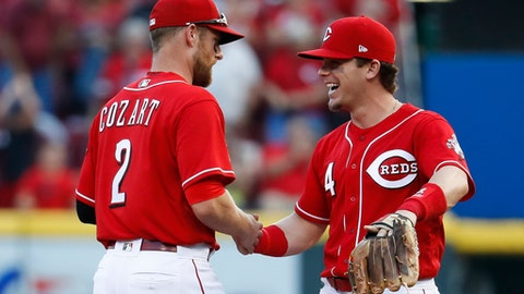 Cincinnati Reds second baseman Scooter Gennett (4) and shortstop Zack Cozart (2) celebrate after closing the ninth inning of a baseball game against the Pittsburgh Pirates, Saturday, Sept. 16, 2017, in Cincinnati. (AP Photo/John Minchillo)