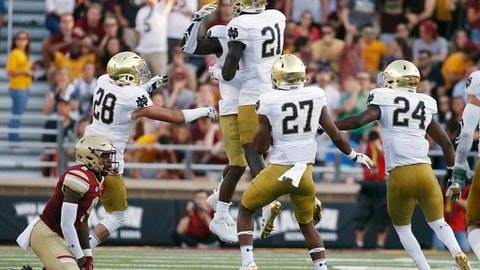 Notre Dame's Shaun Crawford, center behind, celebrates with teammate Jalen Elliott (21) after his interception off Boston College's Kobay White, left, during the second half of an NCAA college football game in Boston, Saturday, Sept. 16, 2017. Notre Dame won 49-20. (AP Photo/Michael Dwyer)