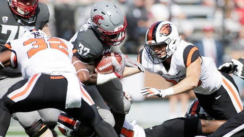 Washington State running back James Williams, center, is tackled by Oregon State linebacker Jonathan Willis, left, linebacker Shemar Smith, bottom, and safety Austin Hudson during the first half of an NCAA college football game in Pullman, Wash., Saturday, Sept. 16, 2017. (AP Photo/Young Kwak)