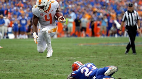 Tennessee running back John Kelly (4) leaps over Florida defensive back Chauncey Gardner Jr. (23) for extra yardage on a run in the second half of an NCAA college football game, Saturday, Sept. 16, 2017, in Gainesville, Fla. Florida won 26-20. (AP Photo/John Raoux)
