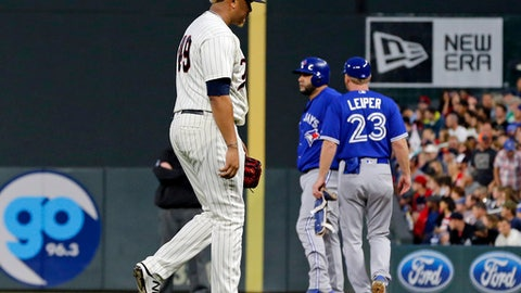 Minnesota Twins pitcher Adalberto Mejia, left, is pulled in the fourth inning of a baseball game after giving up an RBI-single to Toronto Blue Jays' Kendrys Morales, background left, Saturday, Sept. 16, 2017, in Minneapolis. (AP Photo/Jim Mone)