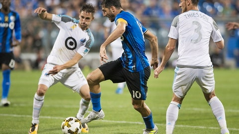 Montreal Impact's Ignacio Piatti, centre, moves by Minnesota United FC's Ethan Finlay (13) and Jerome Thiesson (3) during second half MLS soccer action in Montreal, Saturday, Sept. 16, 2017. (Graham Hughes/The Canadian Press via AP)