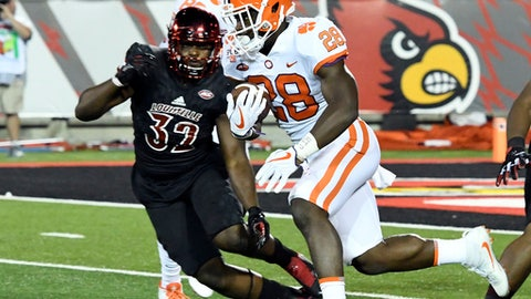 Clemson's Tavien Feaster (28) runs from the defense of Louisville's Stacy Thomas (32) during the first half of an NCAA college football game, Saturday, Sept. 16, 2017, in Louisville, Ky. (AP Photo/Timothy D. Easley)