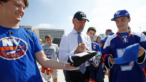 Fans seeking autographs clamor around retired NHL hockey player Bob Nystrom, center, before a preseason NHL hockey game between the New York Islanders and the Philadelphia Flyers in Uniondale, N.Y., Sunday, Sept. 17, 2017. Nystrom is a retired Swedish-born, Canadian professional ice hockey right winger who played for the New York Islanders from 1972–86. (AP Photo/Kathy Willens)