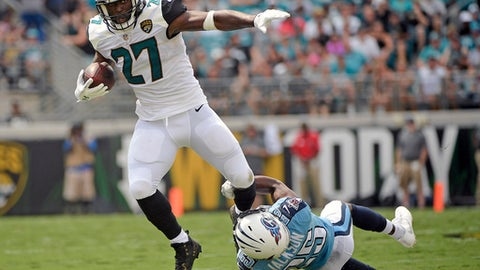 Jacksonville Jaguars running back Leonard Fournette (27) tries to break free from the grasp of Tennessee Titans cornerback Adoree' Jackson on a run during the first half of an NFL football game, Sunday, Sept. 17, 2017, in Jacksonville, Fla. (AP Photo/Phelan M. Ebenhack)