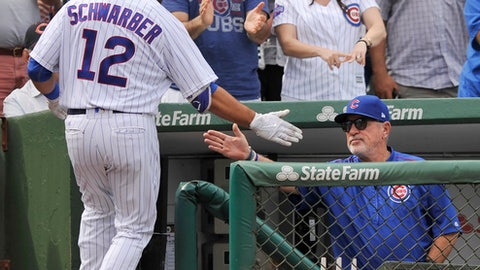 Chicago Cubs' Kyle Schwarber (12) celebrates with manager Joe Maddon right, in the dugout after hitting a solo home run during the fourth inning of a baseball game against the St. Louis Cardinals, Sunday, Sept. 17, 2017, in Chicago. (AP Photo/Paul Beaty)