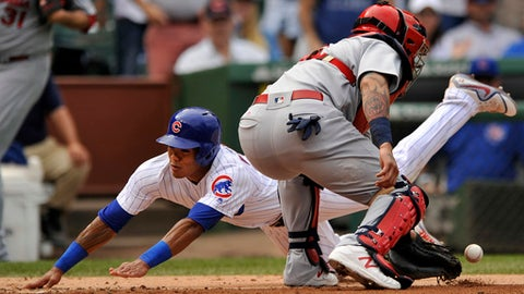 Chicago Cubs' Addison Russell, left, slides safely into home plate on a Ben Zobrist single while St. Louis Cardinals catcher Yadier Molina, right, right, bobbles the throw during the fourth inning of a baseball game Sunday, Sept. 17, 2017, in Chicago. (AP Photo/Paul Beaty)
