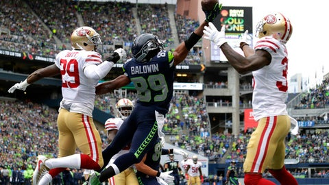 A pass intended for Seattle Seahawks wide receiver Doug Baldwin (89) is broken up by San Francisco 49ers' Dontae Johnson, right, and Jaquiski Tartt, left, in the first half of an NFL football game, Sunday, Sept. 17, 2017, in Seattle. (AP Photo/John Froschauer)