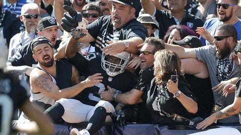 Oakland Raiders running back Jalen Richard, center, celebrates with fans after scoring a touchdown against the New York Jets during the second half of an NFL football game in Oakland, Calif., Sunday, Sept. 17, 2017. (AP Photo/Ben Margot)