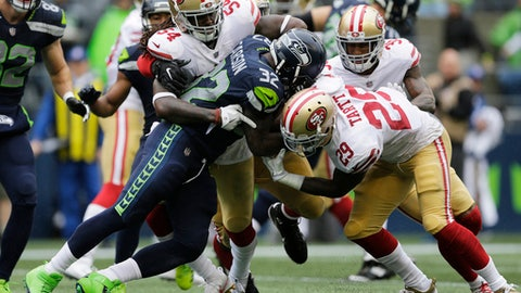 Seattle Seahawks running back Chris Carson (32) rushes against San Francisco 49ers free safety Jaquiski Tartt (29) as he is tackled by 49ers' Ray-Ray Armstrong (54) in the second half of an NFL football game, Sunday, Sept. 17, 2017, in Seattle. (AP Photo/John Froschauer)