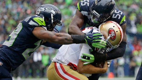 Seattle Seahawks defensive end Frank Clark (55) sacks San Francisco 49ers quarterback Brian Hoyer as free safety Earl Thomas, left, closes in during the second half of an NFL football game, Sunday, Sept. 17, 2017, in Seattle. (AP Photo/Elaine Thompson)