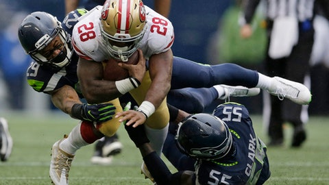 Seattle Seahawks free safety Earl Thomas, left, and defensive end Frank Clark (55) tackle San Francisco 49ers running back Carlos Hyde (28) in the second half of an NFL football game, Sunday, Sept. 17, 2017, in Seattle. (AP Photo/John Froschauer)