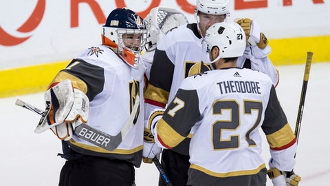 Vegas Golden Knights' goalie Dylan Ferguson, left, Griffin Reinhart (8) and Shea Theodore (27) celebrate their win over the Vancouver Canucks during a preseason NHL hockey game in Vancouver, British Columbia, Sunday, Sept. 17, 2017. (Darryl Dyck/The Canadian Press via AP)