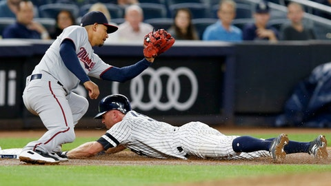 Minnesota Twins third baseman Eduardo Escobar (5) prepares to tag New York Yankees' Brett Gardner, who is safe sliding into third on Aaron Judge's fifth-inning flyout in a baseball game in New York, Monday, Sept. 18, 2017. (AP Photo/Kathy Willens)