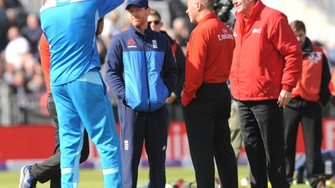 England's captain Eoin Morgan, centre, West Indies captain Jason Holder, left, and umpires inspect the pitch as play is delayed due to a wet outfield before the first Royal London One Day International match between England and West Indies at Emirates Old Trafford in Manchester, England, Tuesday, Sept. 19, 2017. (AP Photo/Rui Vieira)