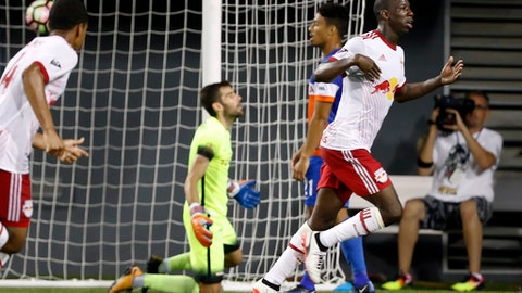FILE - In this Aug. 15, 2017, file photo, New York Red Bulls forward Bradley Wright-Phillips, right, celebrates after scoring on FC Cincinnati goalkeeper Mitch Hildebrandt, center left, in  the second overtime of a U.S. Open Cup semifinal soccer match in Cincinnati. Sporting Kansas City host the New York Red Bulls in the U.S Open Cup final on Wednesday, Sept. 20, 2017. (AP Photo/John Minchillo, File)