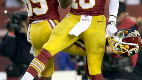 FILE - In this Dec. 3, 2012, file photo, Washington Redskins wide receiver Santana Moss and quarterback Robert Griffin III jump into to each other before an NFL football game against the New York Giants in Landover, Md. Moss, during his weekly radio appearance  in Washington, says Griffin took credit for coach Mike Shanahan and offensive coordinator Kyle Shanahan being fired by the Washington Redskins in 2013. (AP Photo/Evan Vucci, File)