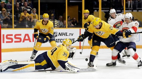 Nashville Predators goalie Anders Lindback (39), of Sweden, reaches to block a shot as right wing Miikka Salomaki (20), of Finland, keeps Florida Panthers right wing Evgenii Dadonov (63) away during the third period of the second game in an NHL hockey preseason doubleheader Tuesday, Sept. 19, 2017, in Nashville, Tenn. The Predators won 3-2 in overtime. (AP Photo/Mark Humphrey)