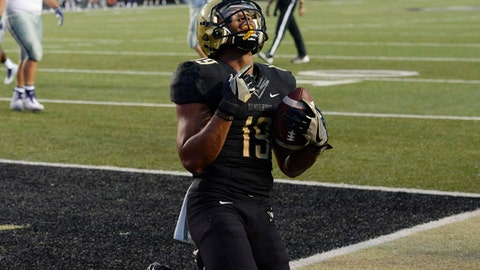 FILE - In this Sept. 16, 2017, file photo, Vanderbilt wide receiver C.J. Duncan (19) kneels in the end zone after scoring a touchdown on a 3-yard pass reception against Kansas State the in the first half of an NCAA college football game, in Nashville, Tenn. Eleven ranked teams play road games against unranked conference rivals this weekend, including No. 1 Alabama against an unbeaten Vanderbilt team that is feeling pretty good about itself after knocking off Kansas State last weekend. (AP Photo/Mark Zaleski, File)