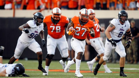FILE - In this Aug. 31, 2017, file photo, Oklahoma State running back J.D. King (27) carries for a 71 yard touchdown during an NCAA college football game against Tulsa in Stillwater, Okla. Oklahoma State's skill position players are racking up the numbers with help from an experienced offensive line that is keeping quarterback Mason Rudolph upright and creating holes for the backs. (AP Photo/Sue Ogrocki, File)