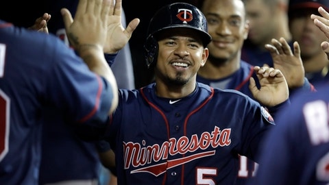 Minnesota Twins' Eduardo Escobar is greeted in the dugout after scoring during the fourth inning of a baseball game against the Detroit Tigers, Thursday, Sept. 21, 2017, in Detroit. (AP Photo/Carlos Osorio)