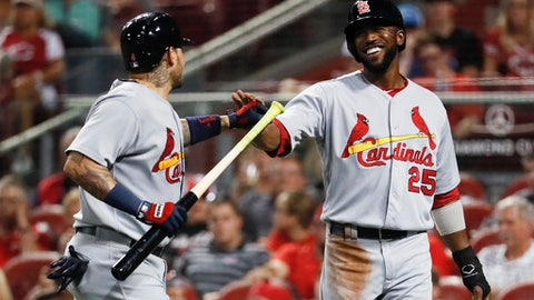 St. Louis Cardinals' Dexter Fowler (25) celebrates after scoring on a sacrifice fly by Yadier Molina, left, off Cincinnati Reds starting pitcher Homer Bailey during the third inning of a baseball game, Thursday, Sept. 21, 2017, in Cincinnati. (AP Photo/John Minchillo)