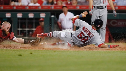 St. Louis Cardinals' Jose Martinez (58) scores on an RBI double by Yadier Molina against Cincinnati Reds catcher Tucker Barnhart, left, during the seventh inning of a baseball game, Thursday, Sept. 21, 2017, in Cincinnati. The Cardinals won 8-5. (AP Photo/John Minchillo)