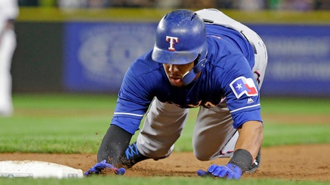 Texas Rangers' Carlos Gomez dives safely back to first base on a pick-off attempt during the sixth inning against the Seattle Mariners in a baseball game Thursday, Sept. 21, 2017, in Seattle. (AP Photo/Elaine Thompson)