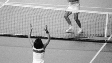 """FILE - In this Sept. 20, 1973, file photo, Billie Jean King raises her arms after defeating Bobby Riggs, rear, getting ready to jump over the net, in the """"Battle of the Sexes"""" tennis match at the Houston Astrodome. (AP Photo, File)"""