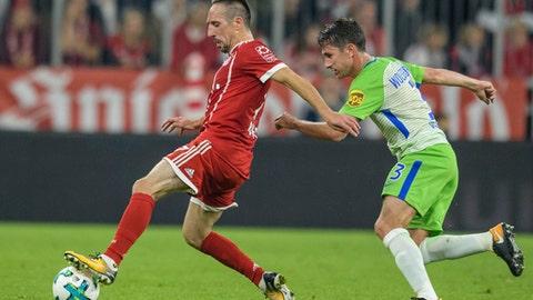 Bayern Munich's Franck Ribery controls the ball with VfL Wolfsburg's Paul Verhaegh, right, during the German Bundesliga soccer match between FC Bayern Munich and VfL Wolfsburg in Munich, Germany, Friday, Sept. 22, 2017. (Matthias Balk/dpa via AP)
