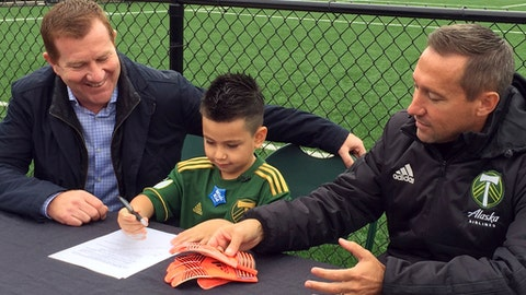 Five-year-old Derrick Tellez, center, signs his contract with Portland Timbers general manager Gavin Wilkinson, left, and coach Caleb Porter, right, on Friday, Sept. 22, 2017, at the Timbers' practice facility in Beaverton, Ore. Tellez, who has had three surgeries for a cancerous brain tumor, was signed to a one-game contract with the MLS soccer team, granting his wish with Make-A-Wish Foundation Oregon. (AP Photo/Anne M. Peterson)