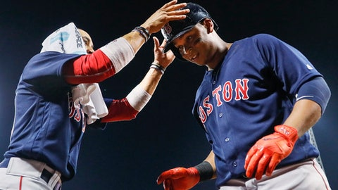 Boston Red Sox's Mookie Betts, left, takes the helmet from Rafael Devers as they celebrate Devers' three-run home run off Cincinnati Reds starting pitcher Sal Romano during the fourth inning of a baseball game, Friday, Sept. 22, 2017, in Cincinnati. (AP Photo/John Minchillo)