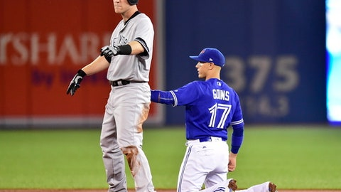 Toronto Blue Jays shortstop Ryan Goins (17) holds the tag on New York Yankees third baseman Todd Frazier (29) after hitting a double during the third inning of a baseball game, Friday, Sept. 22, 2017 in Toronto.  Blue Jays shortstop Ryan Goins used the hidden-ball trick to retire New York Yankees slugger Todd Frazier on Friday night. (Frank Gunn/The Canadian Press via AP)