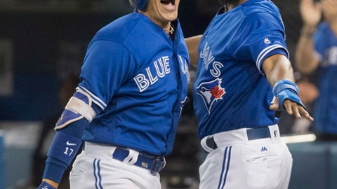 Toronto Blue Jays' Ryan Goins, left, celebrates his grand slam against the New York Yankees with Richard Urena during the sixth inning of a baseball game, Friday, Sept. 22, 2017 in Toronto. (Fred Thornhill/The Canadian Press via AP)