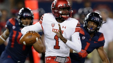 Utah quarterback Tyler Huntley (1) runs away from Arizona pressure during the first half of an NCAA college football game, Friday, Sept. 22, 2017, in Tucson, Ariz. (AP Photo/Rick Scuteri)
