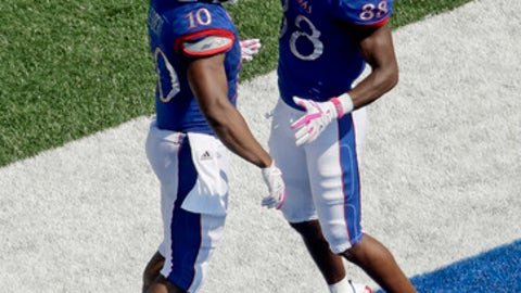 Kansas running back Khalil Herbert (10) celebrates with wide receiver Jeremiah Booker (88) after Herbert scored a touchdown during the first half of an NCAA college football game against the West Virginia, Saturday, Sept. 23, 2017, in Lawrence, Kan. (AP Photo/Charlie Riedel)