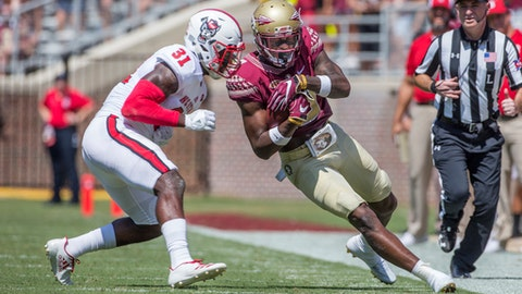Florida State wide receiver Auden Tate closes his eyes before being hit by North Carolina State defender Jarius Morehead in the first half of an NCAA college football game in Tallahassee, Fla., Saturday, Sept. 23, 2017. (AP Photo/Mark Wallheiser)