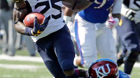 West Virginia running back Justin Crawford (25) gets past Kansas cornerback Derrick Neal (7) as he runs the ball during the first half of an NCAA college football game Saturday, Sept. 23, 2017, in Lawrence, Kan. (AP Photo/Charlie Riedel)