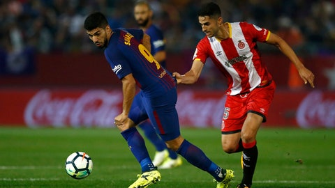 FC Barcelona's Luis Suarez, left, duels for the ball against Girona's Pedro Alcala during the Spanish La Liga soccer match between Girona and FC Barcelona at the Montilivi stadium in Girona, Spain, Saturday, Sept. 23, 2017. (AP Photo/Manu Fernandez)