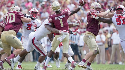 Florida State quarterback James Blackman takes a hit from North Carolina State defensive ends Bradley Chubb as he releases a pass in the second half of an NCAA college football game in Tallahassee, Fla., Saturday, Sept. 23, 2017. NC State defeated Florida State 27-21. (AP Photo/Mark Wallheiser)