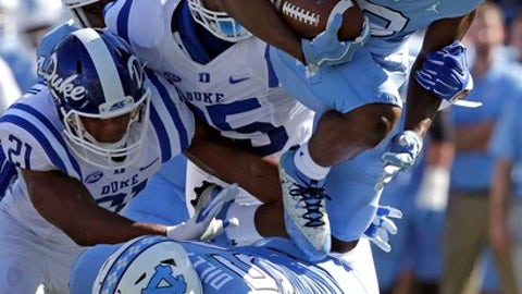 North Carolina's Jordon Brown (2) jumps over Cam Dillard (54) as Duke's Alonzo Saxton II (21) and Trevon McSwain try to make the tackle during the first half of an NCAA college football game in Chapel Hill, N.C., Saturday, Sept. 23, 2017. (AP Photo/Gerry Broome)