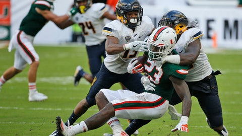 Toledo defensive back Ka'dar Hollman, left, and linebacker Ja'Wuan Woodley, right, take down Miami tight end Christopher Herndon IV (23) during the first half of an NCAA College football game, Saturday, Sept. 23, 2017 in Miami Gardens, Fla. (AP Photo/Wilfredo Lee)