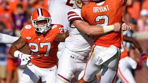 Clemson quarterback Kelly Bryant is pressured in the backfield by Boston College's Kevin Bletzer, front, and Zach Allen during the first half of an NCAA college football game, Saturday, Sept. 23, 2017, in Clemson, S.C. (AP Photo/Richard Shiro)