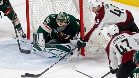 Colorado Avalanche's Brady Shaw, right, tries for a wrap-around shot as Minnesota Wild goalie Devan Dubnyk defends during the first period of a NHL preseason hockey game Saturday, Sept. 23, 2017, in St. Paul, Minn. (AP Photo/Jim Mone)