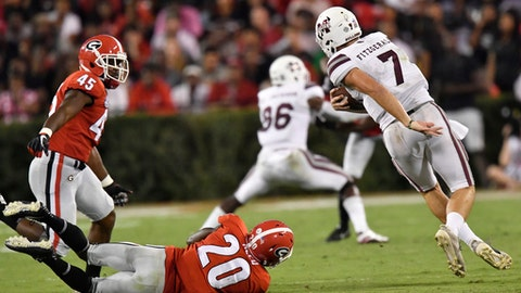 Mississippi State quarterback Nick Fitzgerald (7) runs past Georgia defensive back J.R. Reed (20) during the first of an NCAA college football game, Saturday, Sept. 23, 2017, in Athens, Ga. (AP Photo/Mike Stewart)