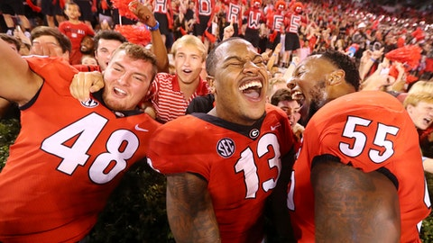 Georgia's Jacob Gross, Jonathan Ledbetter and Dyshon Sims, from left, celebrate a 31-3 victory over Mississippi State with fans after an NCAA college football game Saturday, Sept. 23, 2017, in Athens, Ga. (Curtis Compton/Atlanta Journal Constitution via AP)