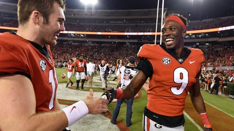 Georgia quarterback Jake Fromm, left, speaks with Georgia wide receiver Jeremiah Holloman (9) after an NCAA college football game against Mississippi State, Saturday, Sept. 23, 2017, in Athens, Ga. Georgia won 31-3. (AP Photo/Mike Stewart)